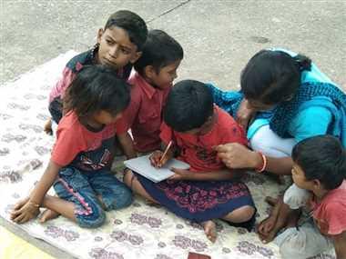 घुमंतू बच्चों को अक्षरज्ञान की सीख दे रहे चाइल्ड लाइन के सदस्य